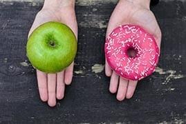 Un donut rose et une pomme verte