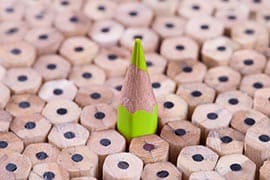 Un crayon vert au milieu d'autres crayons